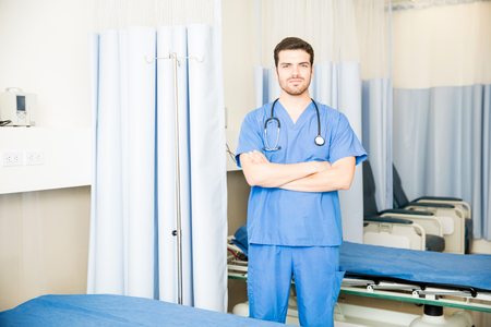 Attractive young doctor in scrubs standing with his arms crossed in a hospital room with couple of empty beds Stock fotó