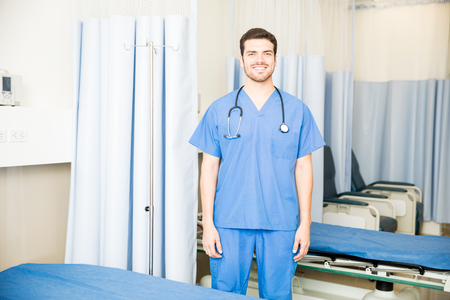 Handsome hispanic doctor wearing scrubs standing in a hospital room