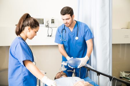 Male doctor supplying oxygen manually with a resuscitator to unconscious patient with nurse standing by the bed