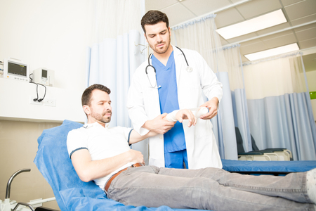 Caring young hispanic doctor applying bandage on wrist of patient in emergency room