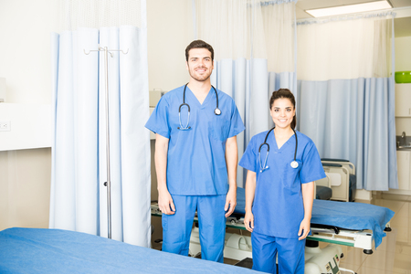 Two young doctors wearing scrubs standing in a empty hospital room 写真素材