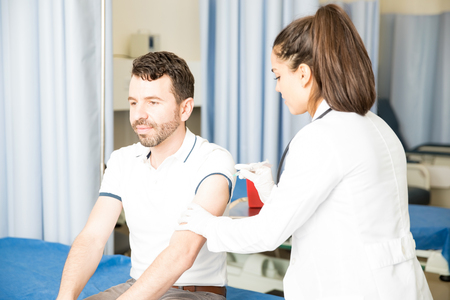Young man with beard sitting on bed in hospital getting an injection on his arm by a female doctor Stock Photo