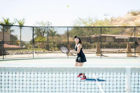 Beautiful young female tennis player aligning herself to hit a winning shot on tennis court