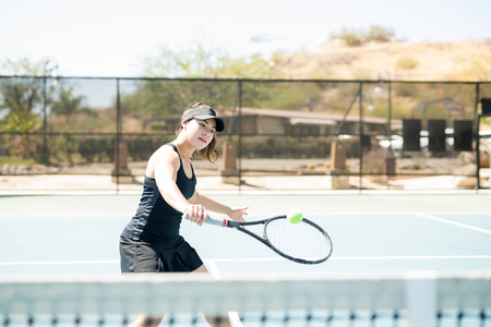 Professional hispanic female tennis player hitting a backhand shot with one hand on court outdoors Stock fotó