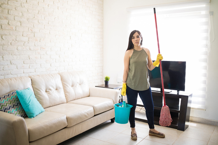 Frustrated woman feeling tired cleaning home with broom