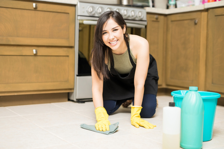 Cute Hispanic housewife cleaning kitchen floor with rug and detergent looking at camera Reklamní fotografie