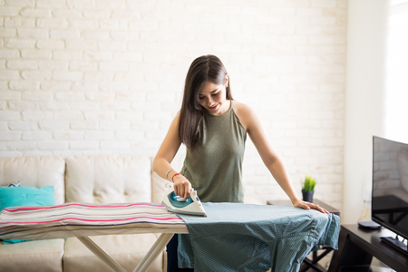Cheerful young housewife wearing casuals ironing men's shirt on ironing board