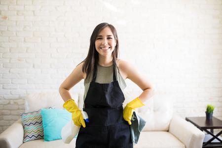 Portret młodej szczęśliwej kobiety w czarnym fartuchu i żółtych rękawiczkach, stojącej trzymając spray i dywan w salonie Zdjęcie Seryjne
