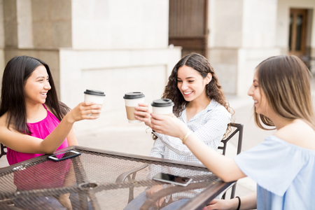 Happy teenage girls having fun and making a toast with coffee at outdoor cafe