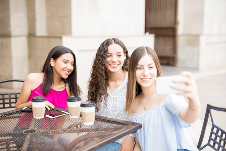 Attractive young girl friends hanging out in a cafe and taking a selfie with a mobile phone Stock Photo