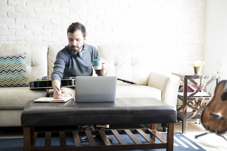 Hispanic male musician sitting on sofa with a cup of coffee writing song in a diary