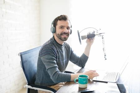 Portrait of handsome young latin man sitting in front of a microphone with laptop at radio station Standard-Bild