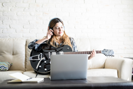 Beautiful young woman listening a new tune on headphones while playing a guitar at home and laptop in front on table Stock fotó