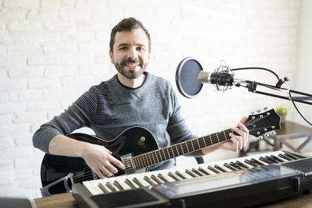 Portrait of handsome young latin man sitting at radio station with guitar and piano
