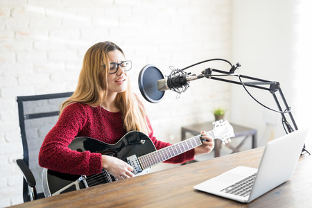 Portrait of beautiful young caucasian woman playing guitar and singing into a micrphone