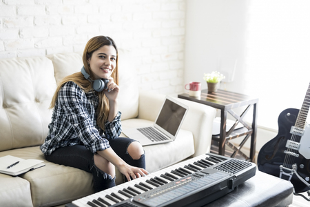 Beautiful woman composing music with electric piano and laptop at home