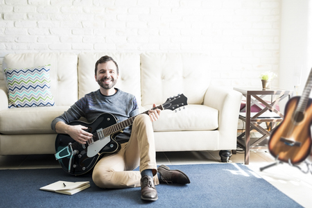 Smiling male music composer sitting on floor with a book and guitar Stock Photo