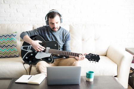 Creative young latin man with headphones playing music on guitar and looking at laptop