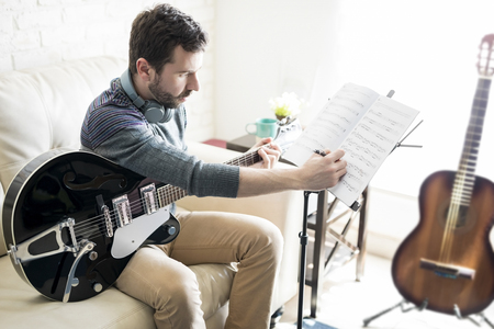 Hispanic man at home studio adding notes on music sheet while composing a new tune