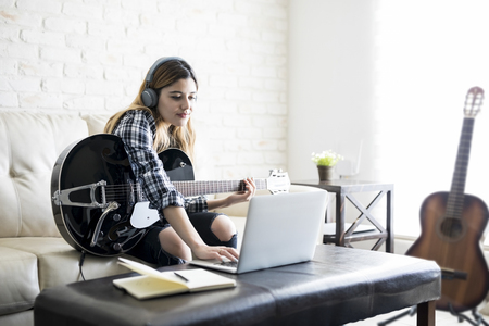 Creative young caucasian woman with guitar using laptop computer at home to compose a song