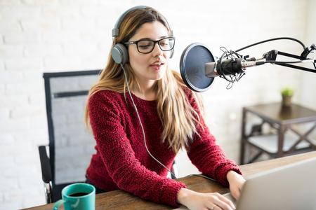 Portret van aantrekkelijke Kaukasische vrouw die hoofdtelefoons draagt en bij online radiostation spreekt Stockfoto