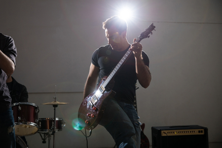 Man playing electric guitar in concert with bright light on stage Фото со стока