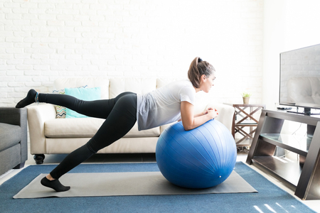 Side view of hispanic woman using the ball for stretching workout at home