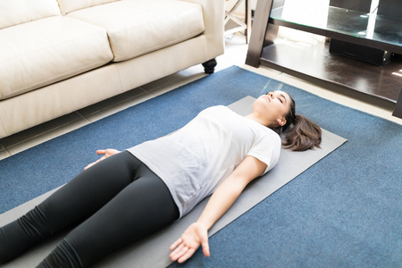 Beautiful hispanic woman practicing yoga dead body pose or savasana pose lying on yoga mat at home.
