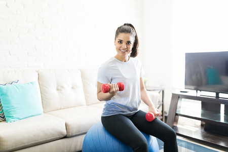 Portrait of attractive latin woman doing arms workout with weights while sitting on swiss ball at home