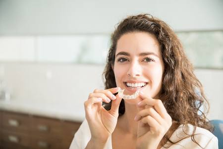 Portrait of beautiful patient holding orthodontic retainers in dental clinic Stok Fotoğraf