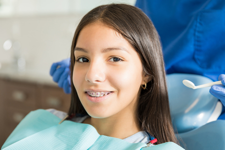 Close-up portrait of smiling teenage girl with braces against dentist standing in clinic Standard-Bild