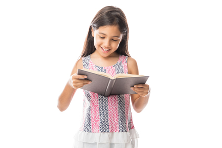 Little smart girl holding a book and reading it while standing against white background