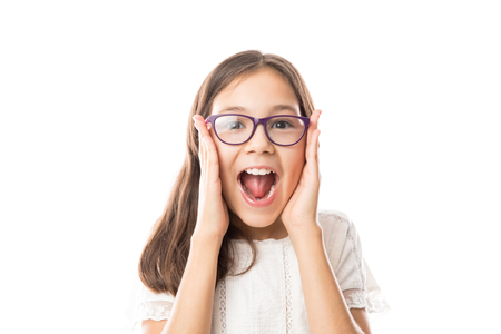 Surprised girl with spectacles holding the sides of her face with her hands and her mouth open in joy
