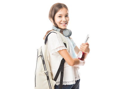 Cute student holding boos with headphones around neck smiling against white background