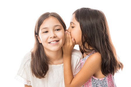 Portrait of two little girls sharing secrets whispering to each other ear while enjoying time together