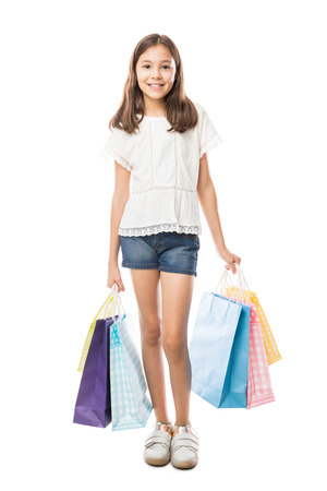 Pretty 10 year old girl with shopping bags in studio against white background