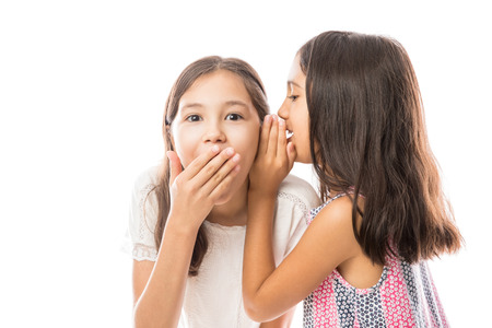 Cute little younger sister sharing funny secret with older sister in ears against white background in studio Stockfoto