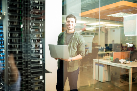 Portrait of happy male technician with laptop in large data center Banque d'images - 104193312