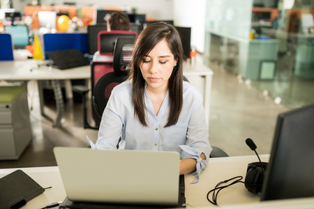 Portrait of young latin woman in casuals working on laptop Stok Fotoğraf