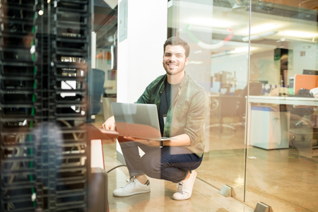 Portrait of happy young male network engineer with laptop in hand working in datacenter. Banque d'images - 104193326