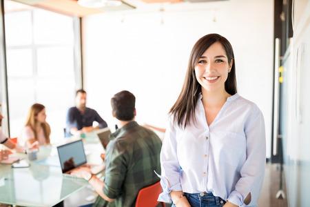 Junge Geschäftsfrau in Freizeitkleidung im modernen Startup-Besprechungsraum