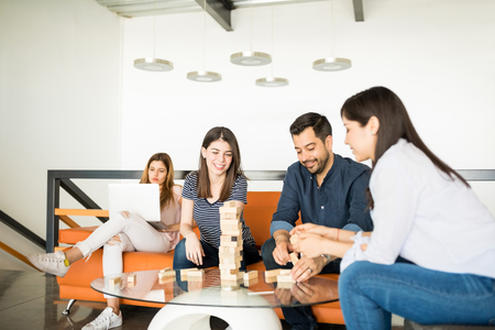Portrait of group of young people in break sitting at office lounge room playing jenga