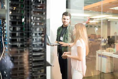 Two business people standing in server room with laptop and discussing Banque d'images - 104230363