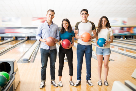 Full length of teenage boys and girls with colorful bowling balls standing in club Stock Photo
