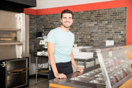 Young waiter in pizza shop standing behind counter smiling looking at camera