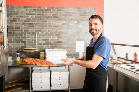 Ritratto di chef sorridente vestita di nero grembiule uniforme azienda ferro grande buccia di pizza con pizza appena sfornata rimossa dal forno nella pizzeria bancone della cucina