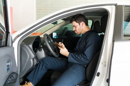 Male technician preparing checklist while sitting in car at an automobile repair shop