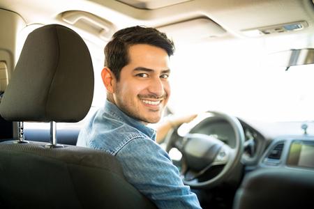 Retrato de apuesto joven hispano sentado en el asiento del conductor del coche y mirando hacia atrás con una cara sonriente Foto de archivo