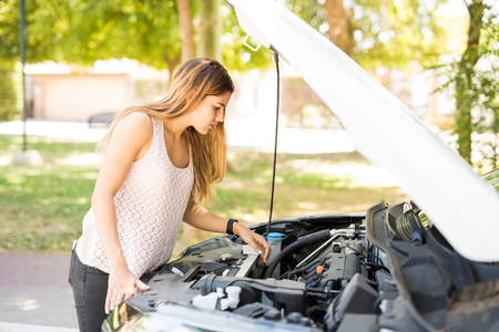 Portrait of young woman looking under the hood of her broken car on street Stock Photo