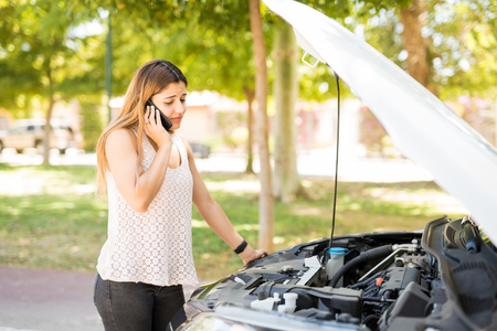 Caucasian woman with a broken car using mobile phone to call assistance on roadside